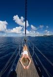 亭亭玉立的白肤金发的妇女在帆船的船首放置 库存照片