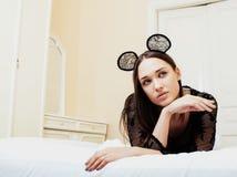 佩带性感的鞋带柳叶蒲公英属的年轻俏丽的深色的妇女,放置等待的作梦在床上 免版税库存照片