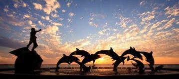 海豚前雕象日落 库存图片