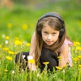 Μικρό κορίτσι στα ακουστικά σε ένα πράσινο λιβάδι χαλάρωση Στοκ Εικόνα