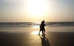 在海滩现出轮廓的两个朋友 免版税库存照片