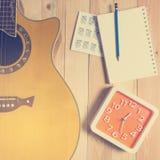 吉他写歌的时刻与一个红色时钟 免版税库存照片