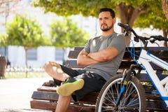坐在公园长椅的男性骑自行车者 免版税库存图片