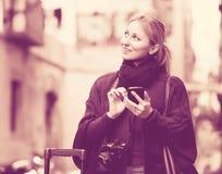 户外移动电话给妇女年轻人打电话 免版税库存图片