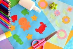 纸章鱼,鱼,海星,螃蟹,花 使用一个色纸的项目想法 孩子的补花工作 免版税库存照片