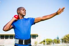 准备男性的运动员投掷铅球球 免版税库存图片