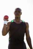 拿着铅球球的男性运动员 免版税库存照片