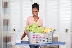 Женщина с утюгом и одеждами в корзине Стоковые Фото