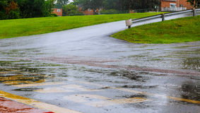 Дождевая вода дороги падает предпосылка с отражением голубого неба и круги на темном асфальте прогноз Стоковые Изображения RF