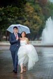 Ευτυχείς νύφη και νεόνυμφος στην άσπρη ομπρέλα γαμήλιων περιπάτων Στοκ εικόνες με δικαίωμα ελεύθερης χρήσης