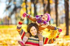 母亲和女儿使用的在秋天公园 图库摄影
