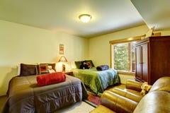 有成对床集合和皮革扶手椅子的明亮的孩子卧室 免版税库存照片