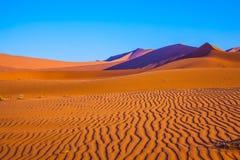 沙丘和含沙橙色波浪 免版税库存图片