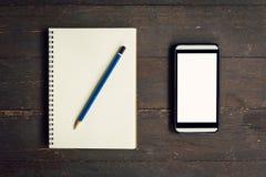 在笔记本和铅笔上的顶视图有电话的 免版税库存照片