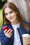 美丽的少妇女孩短信的饮用的咖啡 免版税库存照片