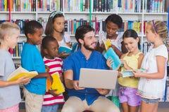 在膝上型计算机的老师教的孩子在图书馆里 图库摄影