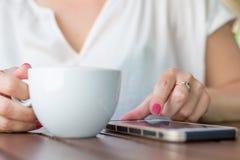 关闭使用她的手机的手妇女在餐馆 免版税库存图片