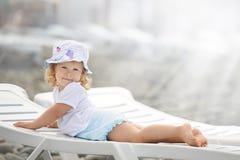 放置在海滩轻便马车的孩子在阳光下长期点燃 免版税库存照片