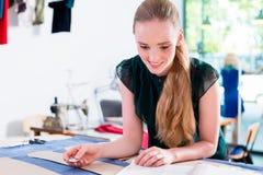 裁缝转移时尚设计的样式到布料 免版税库存照片