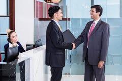 经理欢迎商务伙伴在办公室休息室 免版税图库摄影