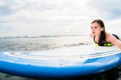 用浆划在冲浪板的女孩冲浪者对公海 免版税图库摄影