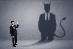 Бизнесмен смотря его собственную концепцию тени демона дьявола Стоковая Фотография