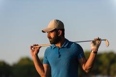 在高尔夫球场的高尔夫球运动员画象日落的 图库摄影