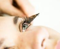 有睫毛引伸的美丽的少妇 与长的睫毛的妇女眼睛 美容师年轻人的睫毛引伸 库存照片