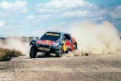 赛车驾驶在一条多灰尘的路的标致汽车 免版税库存照片