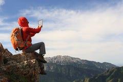 拍在山峰峭壁的背包徒步旅行者用途数字式片剂照片 免版税库存图片