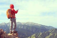 拍在山峰峭壁的妇女背包徒步旅行者用途数字式片剂照片 免版税库存照片