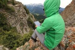 拍在山峰峭壁的妇女背包徒步旅行者用途数字式片剂照片 图库摄影