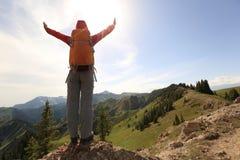 步行在山峰峭壁的妇女背包徒步旅行者 库存图片