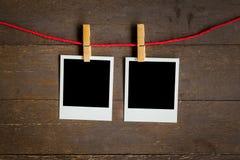 两垂悬在木背景的空白的照片框架 库存照片