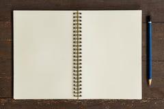 与铅笔的布朗开放书在木头 免版税库存照片