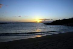 Όμορφο ηλιοβασίλεμα πέρα από τον ωκεανό με τα κύματα που κινούνται προς την παραλία Στοκ Εικόνες