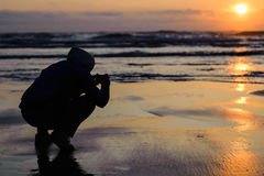 Заход солнца бдительности накидки при силуэт человека фотографируя на заходе солнца Стоковое Изображение