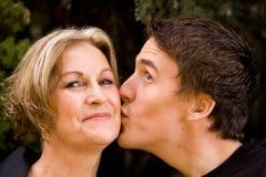 产生愉快的亲吻妈妈微笑的儿子 免版税图库摄影
