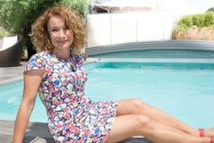 说谎在游泳池旁边的逗人喜爱的白肤金发的妇女 免版税图库摄影