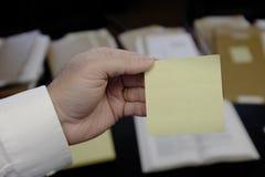 拿着空白的稠粘的笔记的手 免版税库存照片