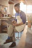 男性陶瓷工坐凳子使用膝上型计算机 库存照片