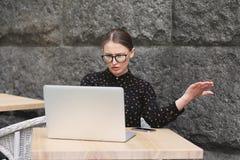戴眼镜,在调查膝上型计算机的咖啡馆的黑衬衣的惊奇的妇女 图库摄影