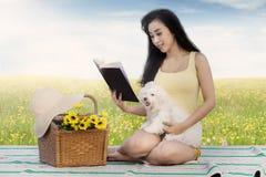 妇女和狗在草甸读了书 免版税库存图片