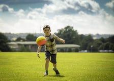 踢橄榄球的小男孩在公园 图库摄影