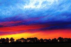 Яркий заход солнца красит сельскую местность Стоковые Изображения