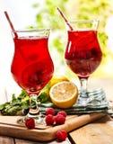 在木是与莓果鸡尾酒的冰冷的饮料玻璃 免版税库存照片