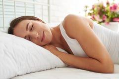 平安地睡觉在她的床上的少妇面对在照相机 库存图片