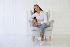 坐在一把现代扶手椅子的少妇放松在她的屋子里 免版税图库摄影
