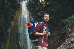 在瀑布旁边的人在迁徙的山以后 库存照片
