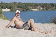 棒球帽和沐浴的成熟人短缺说谎在含沙 免版税库存图片